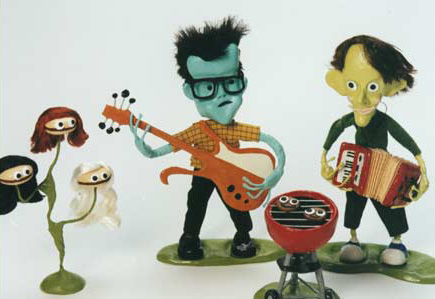 Painted clay sculptures playing bright, wonky instruments. JF's skin is light blue and JL's is pale yellow.
